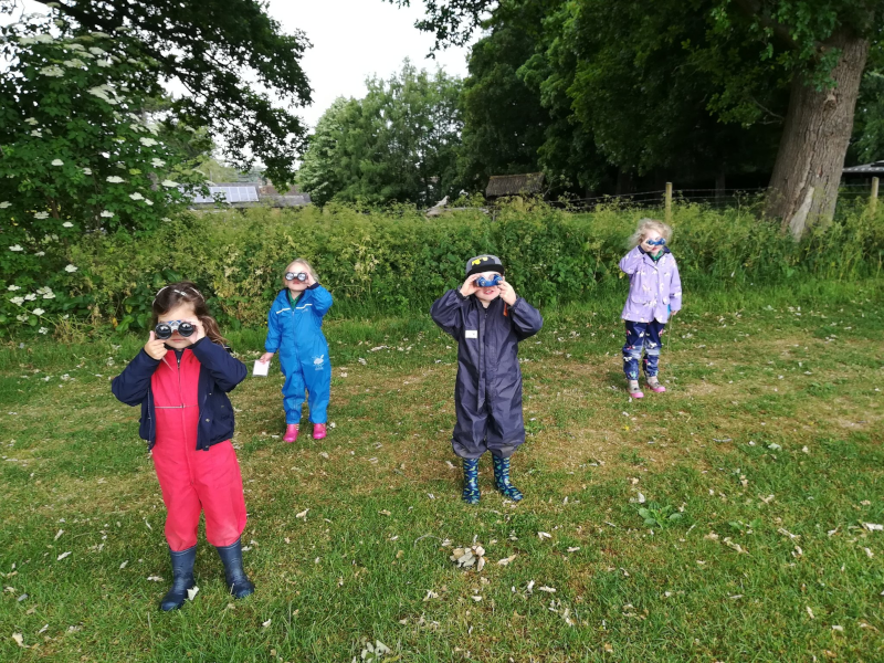 Sibford school students outdoors with binoculars